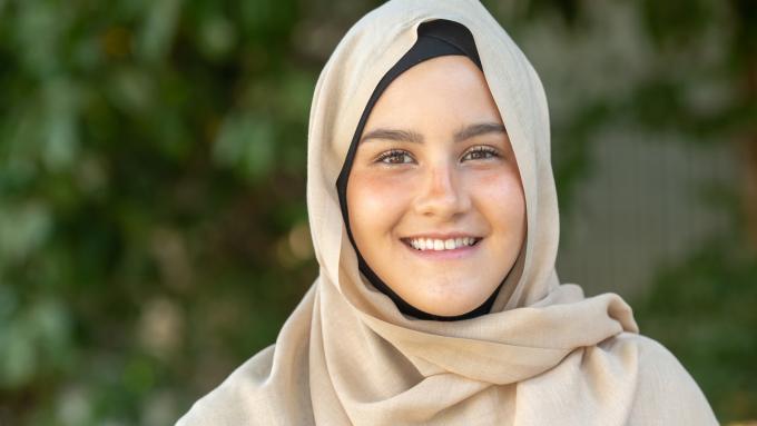 Muslim teenage girl smiling at the camera