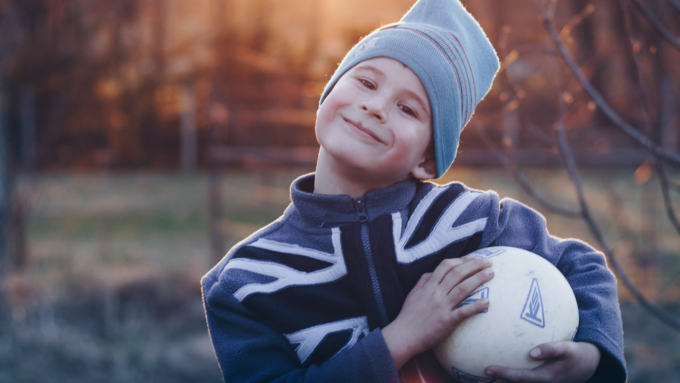 Young boy smiling and holding football