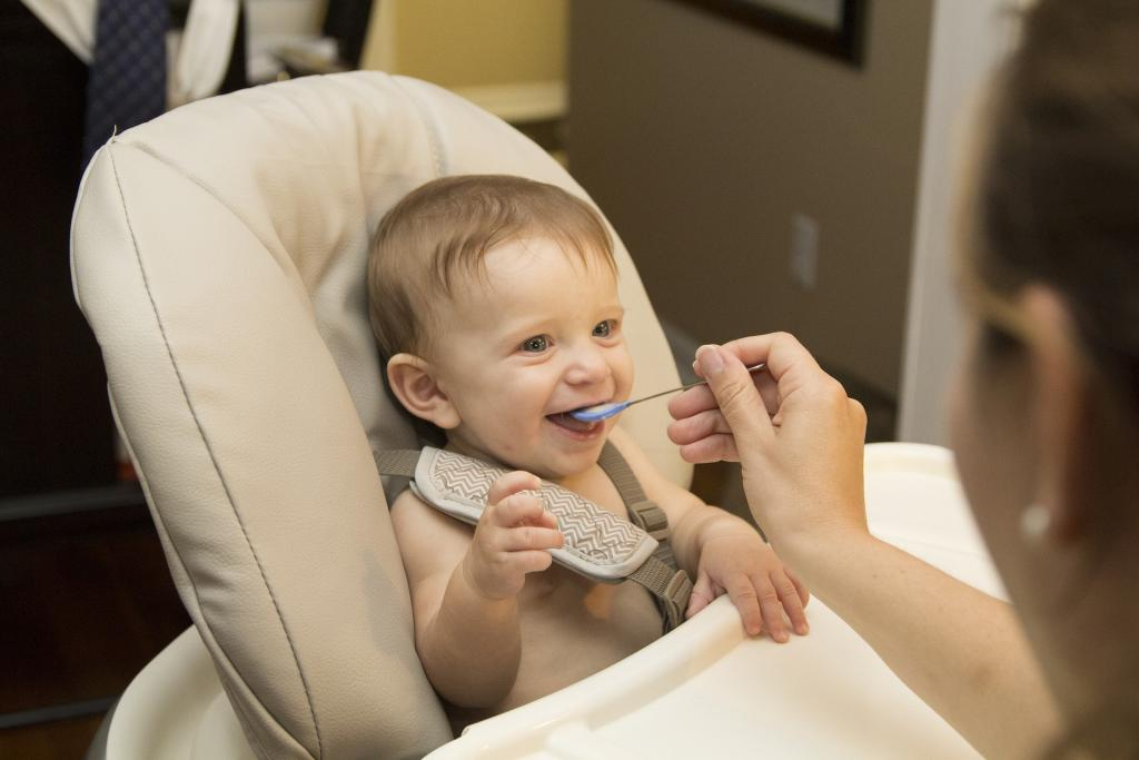 Baby being fed in highchair