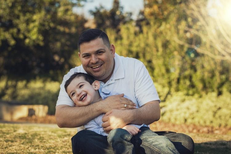 Father holding son and laughing