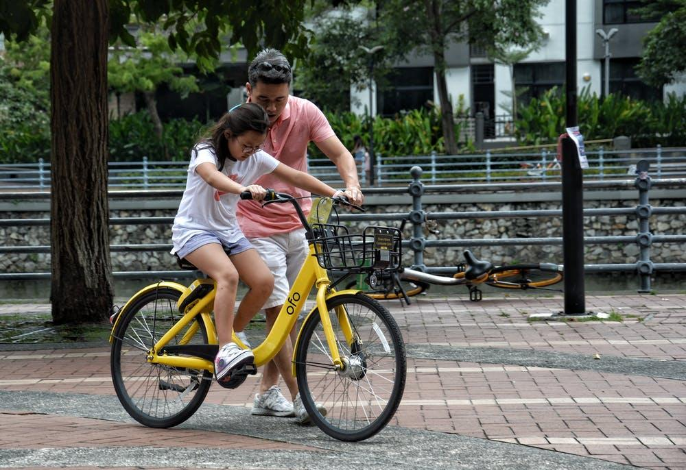 Girl being taught to ride a bike