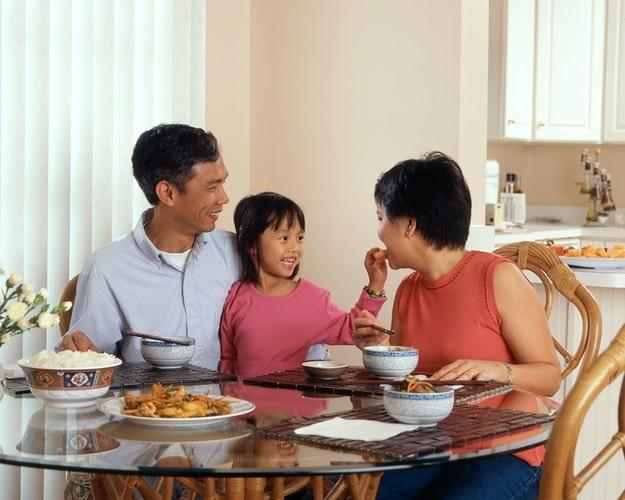 Family smiling around dining table as young girl feeds her mother