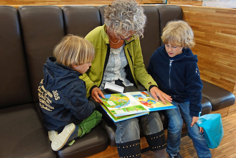Grandmother reading book with grandchildren