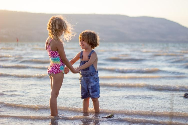 Young siblings holdings hands on a beach