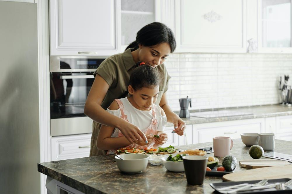 Young girl and her mother cooking a healthy meal